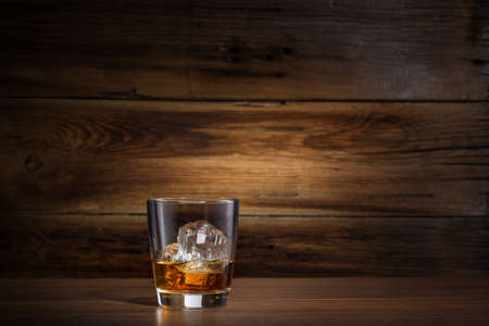 shot: glass of whiskey with ice on a wooden background