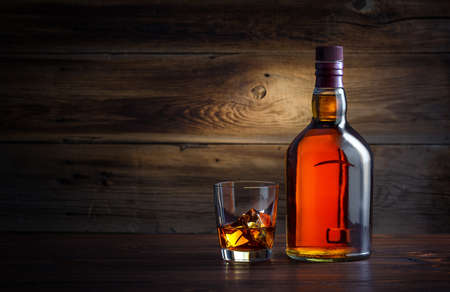 bottle and glass of whiskey with ice on a wooden background