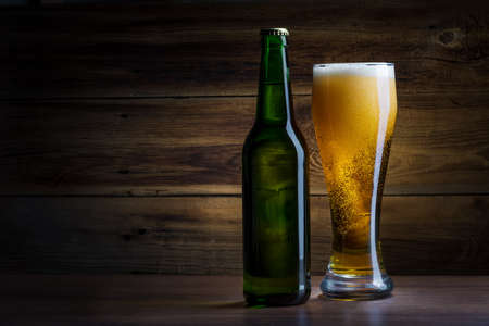 bottle of beer on a wooden background photo