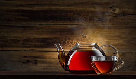glass teapot with black tea on wooden background photo