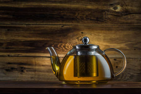 glass teapot with green tea on a wooden background