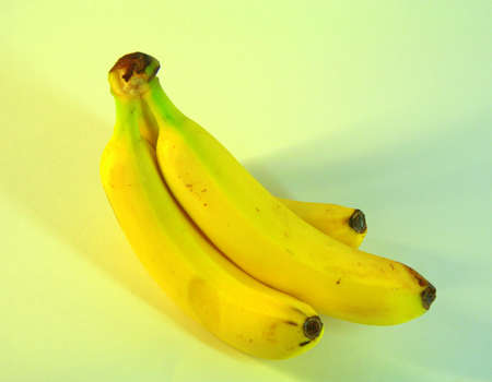 A bunch of ripe, delicious bananas, three pieces. The picture was taken in the lightbox, close-up. Stock Photo