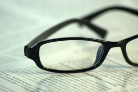 Black-framed glasses lie on the page of the magazine. Close up.