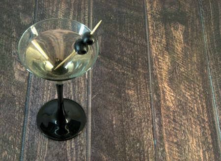 A full martini glass with two olives on a toothpick stands on a wooden table. Close-up.