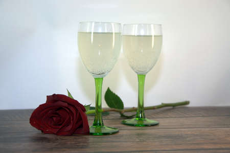Two glasses of champagne and a red rose on a wooden table. Close-up.