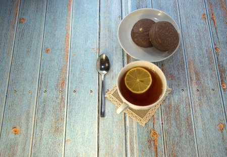 A cup of tea with lemon, a spoon and two chocolate cakes on a plate lie on a wooden table. Close-up.