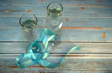 Two glasses of champagne, connected by a blue satin ribbon on a wooden table. Close-up.