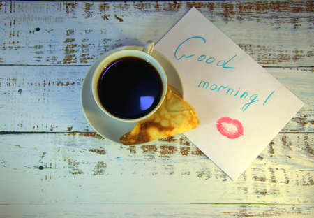 A cup of coffee on a saucer, a freshly baked pancake and a piece of paper with a wish of good morning and a trace of lipstick. Close-up.
