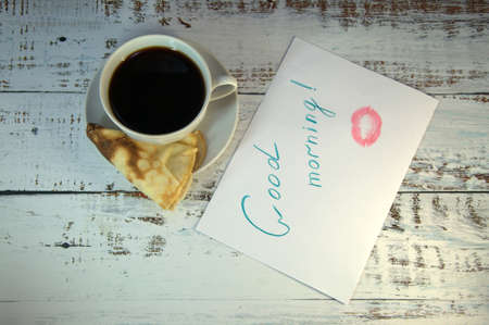 A cup of coffee on a saucer, a freshly baked pancake and a piece of paper with a wish of good morning and a trace of lipstick. Close-up. Stok Fotoğraf - 118410111