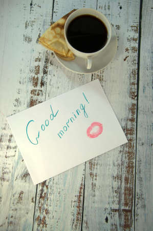 A cup of coffee on a saucer, a freshly baked pancake and a piece of paper with a wish of good morning and a trace of lipstick. Close-up. Stok Fotoğraf - 118410135
