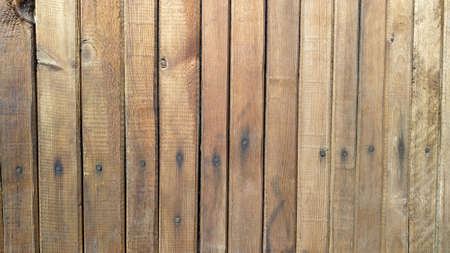 Old wooden fence of tightly fitted boards, with traces of nail heads. Background, texture.
