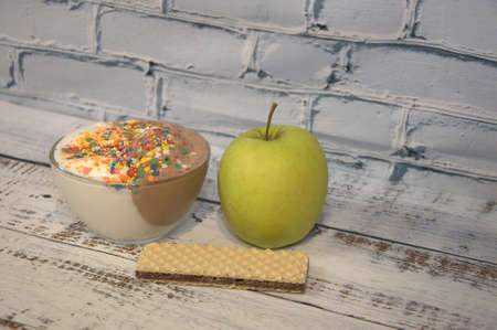 Chocolate and vanilla ice cream with decor, green apple and waffle lie on a wooden table. Imagens - 131561278
