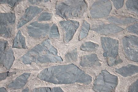 A wall of roughly treated cobblestone bonded with cement mortar. Stok Fotoğraf