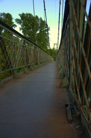 The pedestrian part of the suspension bridge against the evening sky.