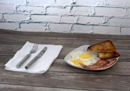 A plate with fried eggs, bacon and croutons stands on the table next to a napkin with a knife and fork.