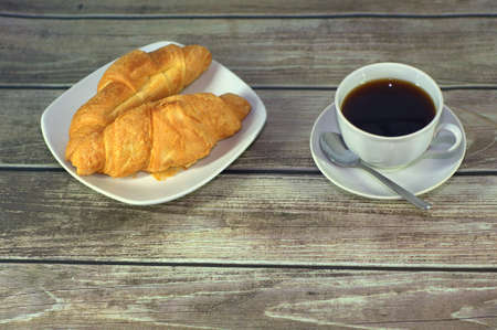 Two croissants on a ceramic plate and a cup of black coffee on the table by the brick wall. Фото со стока