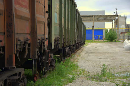 Railroad cars in a dead end at an old abandoned factory at the blue gate of the warehouse.