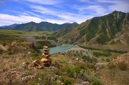 Sacral cairn on top of a hill overlooking the mountains and the river. Katun, Altai, Siberia, Russia.