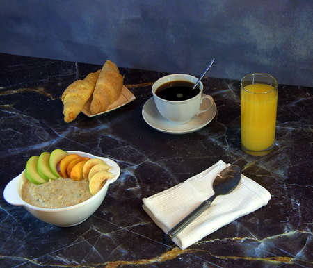 Traditional healthy breakfast, oatmeal with fruits, a cup of black coffee, two croissants and a glass of orange juice. Zdjęcie Seryjne