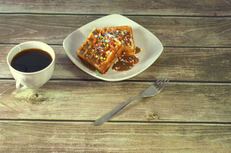 A cup of black coffee, a fork and a plate with two Viennese waffles. Фото со стока