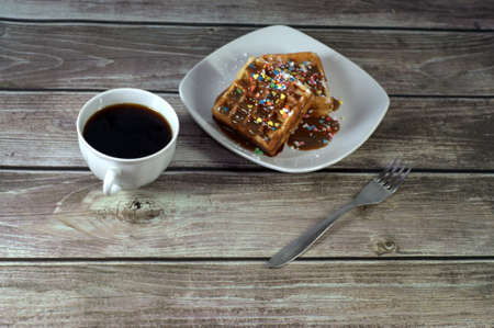 Plate with two Viennese waffles in icing and a cup of black coffee. Close-up.