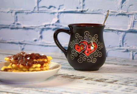 A dark ceramic mug with tea and a stack of waffles on a saucer with strawberry jam. Close-up. Фото со стока