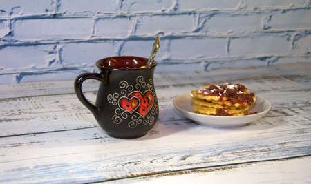 A mug of herbal tea with lemon and saucer with a stack of waffles with strawberry jam. Close-up.