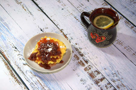 A mug of tea with lemon and a plate of waffles with strawberry jam. Close-up.