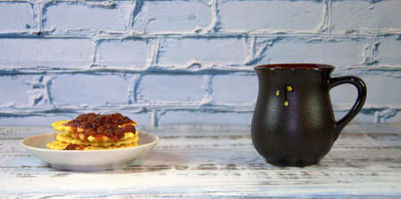 Dark ceramic cup with tea, next to a plate with waffles with strawberry jam. Close-up. Фото со стока