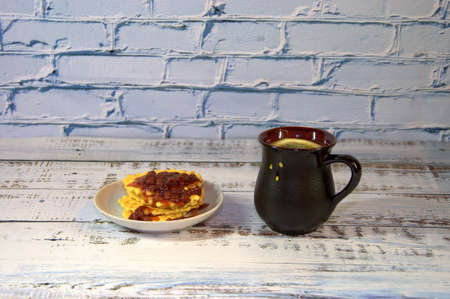 A brown ceramic cup with hot tea and a plate of waffles with strawberry jam. Close-up.