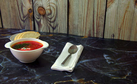 Traditional Russian soup Red Borsch , sliced wheat bread, white textile napkin and spoon. Close-up. Stock Photo