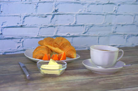 A hearty breakfast, a cup of black coffee, two croissants, slices of orange and butter. Close-up. Archivio Fotografico - 131657459