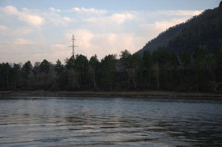 A high electric pole on the banks of a calm river surrounded by evening forest. Altai, Siberia, Russia.