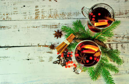 Warm Christmas composition, two glasses of mulled wine with spices, orange and apples, on a table surrounded by fir branches and cones. Close-up.