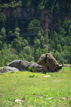 A power line pillar in front of a chopped cobblestone in a clearing at the foot of high rocky mountains. Altai, Siberia, Russia. 版權商用圖片