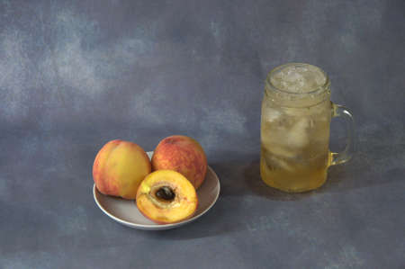 Three peaches, two whole and one cut in half, lie on a white saucer, next to a mug of juice with ice. Close-up. 写真素材