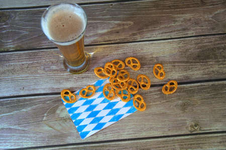 A tall glass of light beer on a traditional napkin and a group of salty pretzels. Close-up. Stock Photo