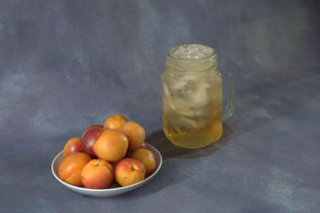 A mug of juice with ice and a plate with apricots and peaches. Close-up.
