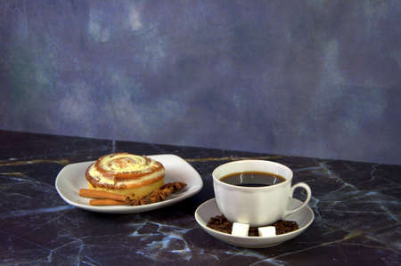 A white ceramic cup with fresh coffee on a saucer decorated with grains and sugar cubes on a table next to a plate with a cinnamon roll in the glaze. Close-up.