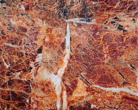 Brown granite, polished surface of natural stone with white veins and blotches. Close-up.