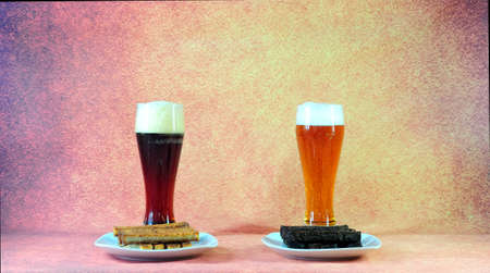 Two tall glasses with dark and light beer with white foam stand in front of two plates with wheat and rye croutons. Close-up.