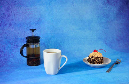 Sweet breakfast, tea cup plate with sponge cake in chocolate chips with cherries and tea teapot on a blue abstract background. Close-up.