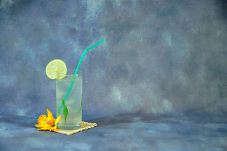 A tall glass of mojito with ice stands on a textile stand next to a vanilla flower bud the whole composition on a gray abstract background. Close-up.
