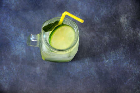 A glass mojito mug with ice, a slice of lime and a drinking tube are on a gray background. Close-up.