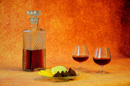 Crystal decanter with cognac and two glasses of drink next to a plate with appetizers, cut lemon and chocolate candies. Close-up.