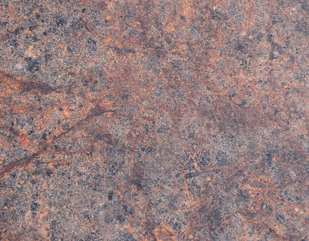 Brown granite, polished surface of natural stone with black veins and interspersed close-up. Background.