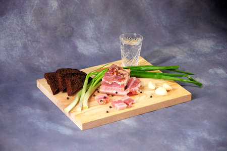 A wooden stand with a yummy vodka piece of lard with green onions, garlic and pepper is on a gray background. Close-up. Imagens