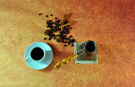 A cup on a saucer with hot coffee, an old-fashioned copper turk and coffee beans on a brown background. View from above.