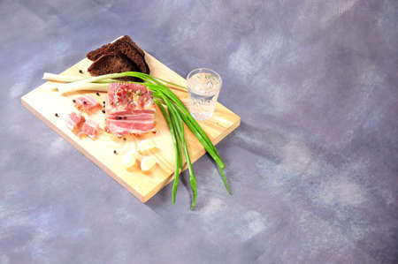 Wooden board with a glass of vodka, a piece of bacon, green onions, garlic and rye bread on a gray background. Close-up. Imagens