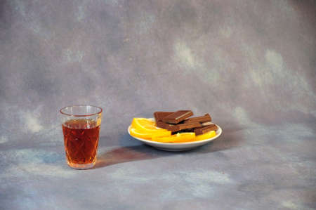 Crystal glass of cognac and a plate with slices of lemon, chocolate and nuts in the foreground. Gray abstract background.